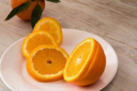 Oranges and Orange Slices on white plate with leafs on white marble. Citrus Food Photography.