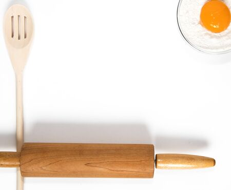 Wooden Spoons and rolling pin for baking and cooking with flower and egg yolk.  Top View on white background