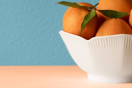 Fresh oranges in white porcelain Bowl. Healthy Citrus fruits on blue background. Kitchen Concept Reklamní fotografie