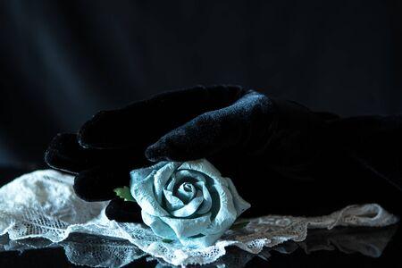 Black Velvet glove with blue paper rose and lace scarf on black background. Elegance Concept