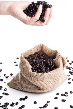 Coffee Beans in female hand over jute bag  on white backgrou