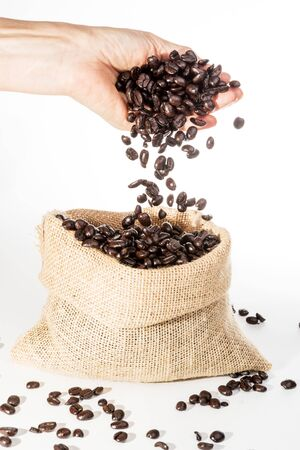Coffee Beans falling into jute bag from female hand on white background Reklamní fotografie