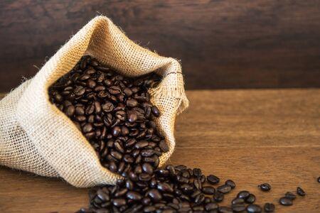 Roasted Coffee Beans spilled from Jute Bag on wooden boards Reklamní fotografie