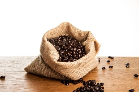 Roasted Coffee Beans spilled from Jute Bag on wooden boards with white background Reklamní fotografie