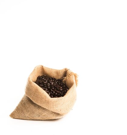 Roasted Coffee Beans in Jute Bag on white background with Copy Space.