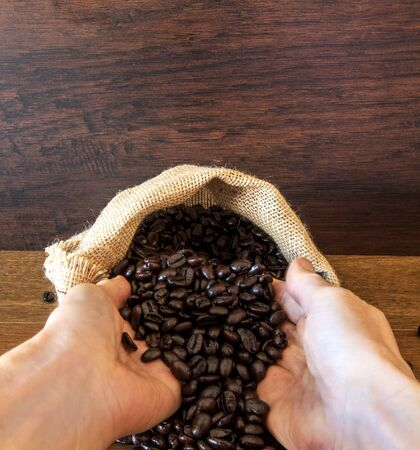 Hands hold Coffee Beans in bag on wooden background.