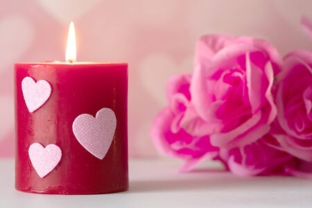 Valentines Day still life with  candle, and pink roses. Romantic Concept on pink soft background.