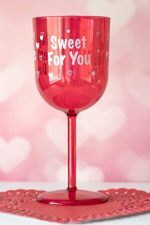 Valentines Day still life with red glass. Romantic Concept on pink soft background.