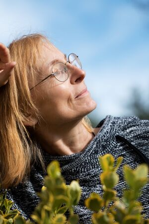 Serene Senior woman with glasses looking towards the sun.  Older woman
