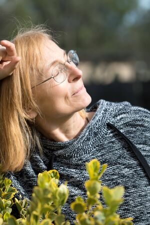 Senior woman with closed eyes enjoys outside with face towards the sun. Older woman with glasses