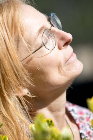Serene Senior woman with closed eyes enjoys outside with face towards the sun. Older woman with glasses
