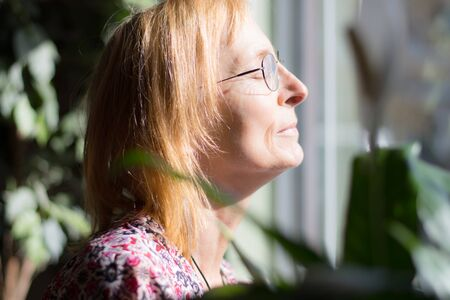 Serene Senior woman with closed eyes enjoys outside sun through window. Older woman with glasses