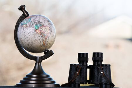 Globe and vintage binoculars on blurred background.  Travel and discovery concept