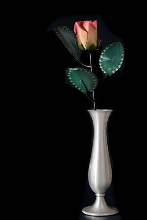 Metal rose in silver vase isolated on black background