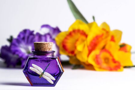 Purple Glass  Bottles with Vintage cork lid and dragonfly picture on white background with blurred purple and yellow flowers. wooden boards. Glass Container