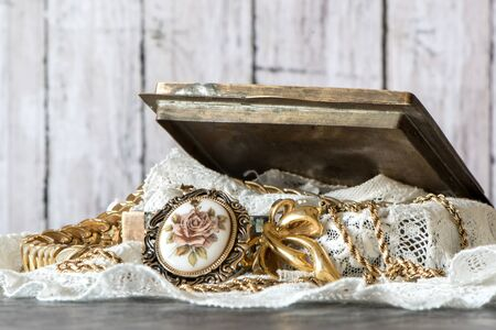 Metal Open Jewelry Box with pile of golden jewelry and lace against wood background