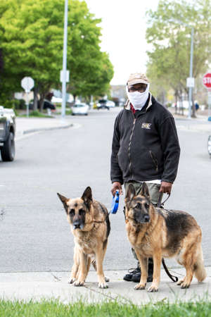Santa Rosa, USA April 9, 2020 - Man with self made mask walks German Shepherd dogs. Concept of Lockdown, Flatten the Curve, Social Distancing, State of Emergency