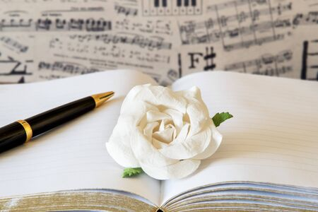 White paper rose on note book with black and gold pen against musical note wallpaper. Banque d'images