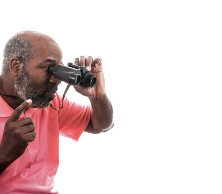 African American man looking through binoculars on white background with copy space. Foto de archivo