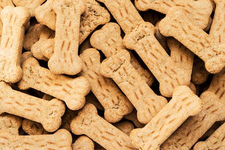 Pile of Bone shaped dog biscuits of brown color. Abstract wallpaper.