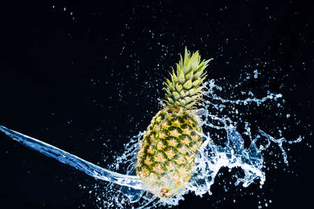 Fresh pineapple gets splashed with water on black background. Concept of summer, health and fun