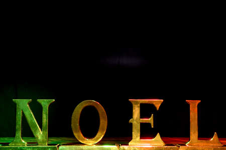 Christmas decoration with gold green red noel sign on black background. Stock Photo