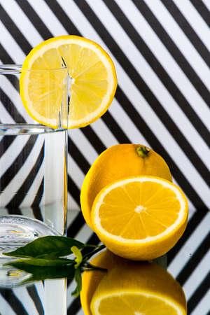 Highball glass with a lemon wagon wheel garnish against black and white striped background Banque d'images