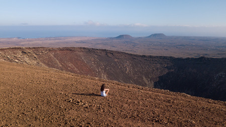 girl sitting on the top of a volcano, fuerteventura