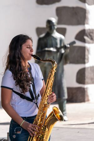 young girl plays the saxophone in the city of Lanos de Aridane