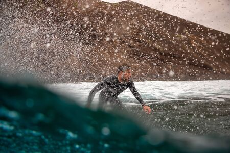 Surfer riding waves on the island of fuerteventura in the Atlantic Ocean, Canary Islands