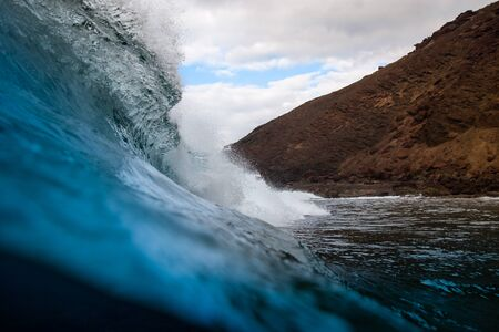 breaking wave with the tube and blue water with the clouds at the background