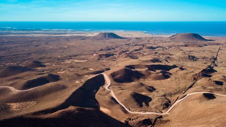 Aerial view of a road leading through vast area of volcanic land and mountains Stock Photo