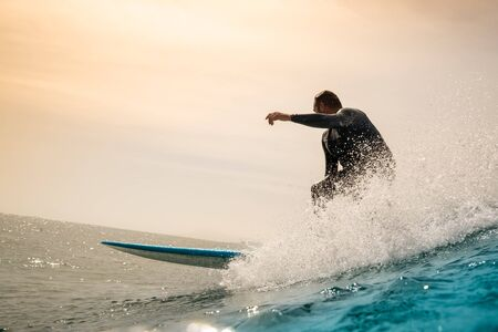 Surfer riding waves on the island of fuerteventura in the Atlantic Ocean, Canary Islands Stock Photo