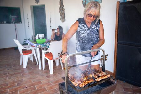 happy elderly lady cooking on a barbecue in the garden together with her family Stock Photo