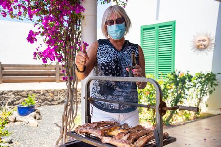 elderly lady cooking on a barbecue with face mask Stock Photo