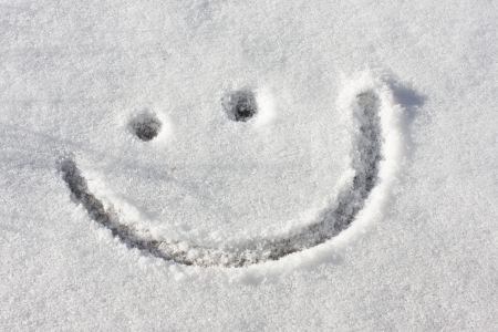 drawing of smiley face in white snow on the ground photo