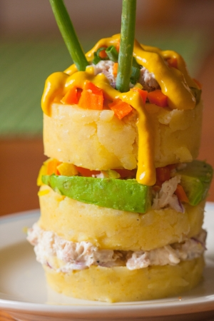 Peruvian-style traditional dish causa de pollo made out of layers of yellow potatoes with chicken