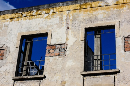 falling apart building with iron bars in the windows showing blue sky in the background