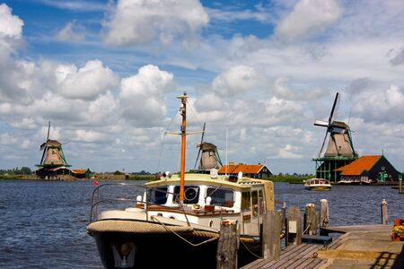 Dutch wind mill and a boat on the water side photo