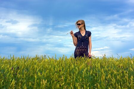 Cute young blond girl on a field in summer, blue sky photo