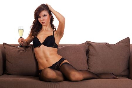 brunette girl in black underwear laying on a sofa with a glass of white wine, isolated photo