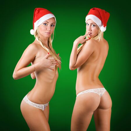 hat nude: two cute sexy topless blond girls wearing santa claus cap green background Stock Photo