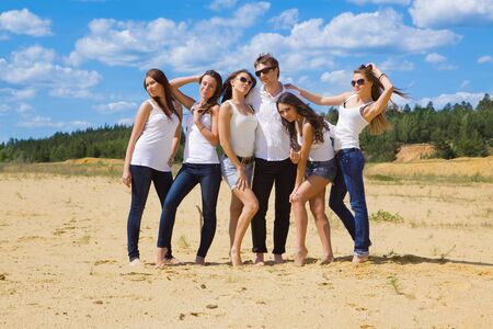 Group of six friends all in blue jeans and white photo