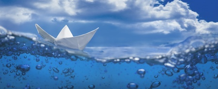 paper boat: paper ship splash with bubbles sailing in blue water and sky