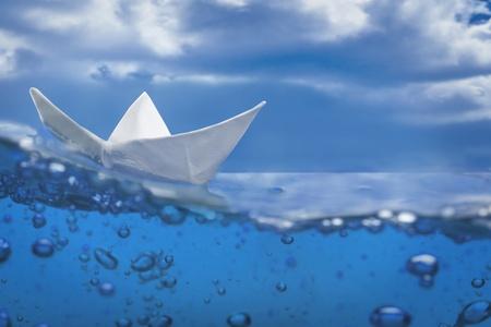 the boat on the river: salpicaduras de barco de papel con burbujas navegando en el agua azul y el cielo