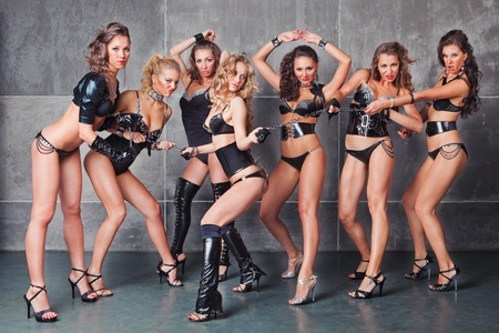Seven Cute go-go sexy girls in black with diamonds costume pulling a chain photo