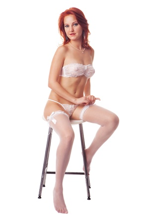 nude girl sitting: Beautiful and sexy red hair girl wearing white lingerie sitting on a bench isolated on white background
