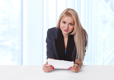 Portrait of an attractive young businesswoman holding a contract paper and smiling at her desk photo