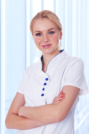 Portrait of a confident young dentist lady standing with folded hand in the hospital  photo
