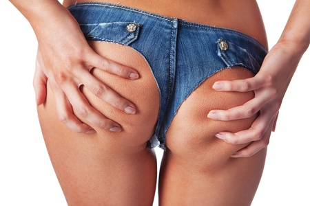 close up of woman holding with her hands buttocks in denim shorts isolated over white background Stock Photo - 13288837